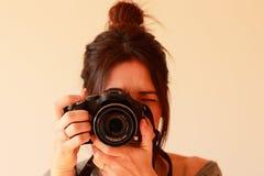 Junger weiblicher Fotograf mit Kamera auf weichem Hintergrund Stockbild
