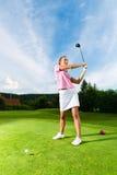 Junger weiblicher Golfspieler auf dem Kurs, der Golfschwingen tut Stockbild