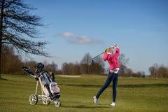 Junger weiblicher Golfspieler, der auf der Fahrrinne spielt Lizenzfreie Stockfotografie