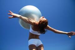 Junger weiblicher Gymnast mit Yogakugel auf ihrem Kasten Lizenzfreies Stockfoto
