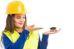 Junger weiblicher Ingenieur, der kleines Haus hält lizenzfreie stockfotos