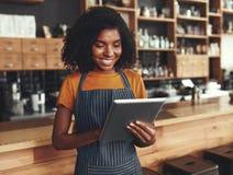 Junger weiblicher Inhaber, der digitale Tablette bei der Stellung im Café verwendet lizenzfreie stockbilder