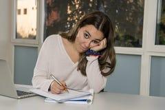 Junger weiblicher Jugendlichhochschulstudent, der in der Schule mit dem Klassenzimmer des Computerlaptops sitzt auf dem studieren Lizenzfreie Stockbilder