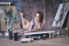 Junger weiblicher Künstler, der abstraktes Bild im Studio, schönes sexy Frauenporträt malt Lizenzfreies Stockbild