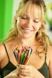 Junger weiblicher Künstler, der farbige Bleistifte und das Lächeln betrachtet Stockbilder