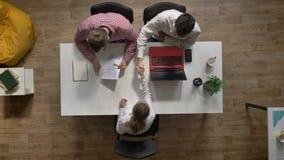 Junger weiblicher Kandidat für Job geinterviewt von zwei Arbeitgebern, topshot, bei Tisch sitzend im modernen Büro, Interview stock footage