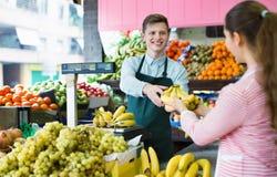 Junger weiblicher Kunde, der gelbe Bananen kauft Lizenzfreie Stockfotografie
