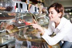 Junger weiblicher Kunde, der köstlichen Nachtisch wählt Lizenzfreie Stockfotos