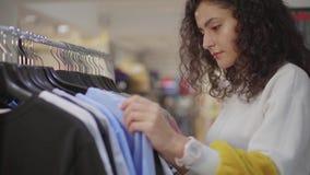 Junger weiblicher Kunde, der Kleidung w?hlt stock footage