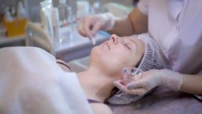 Junger weiblicher Kunde erh?lt Sch?nheitsgesichtsbehandlungsverfahren Gesichtserneuerung Kosmetiker benutzt Baumwollknospe, um Ge stock video