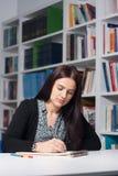Junger weiblicher Kursteilnehmer in der Bibliothek Lizenzfreie Stockfotografie
