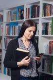 Junger weiblicher Kursteilnehmer in der Bibliothek Stockfotografie