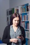 Junger weiblicher Kursteilnehmer in der Bibliothek Lizenzfreie Stockfotos