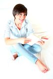 Junger weiblicher Kursteilnehmer, der ein Buch liest Stockbild