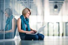 Junger weiblicher Kursteilnehmer mit einem Laptop Stockfotografie