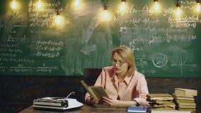 Junger weiblicher Lehrer in den Gläsern, die an einem Tisch im Volksschuleklassenzimmer sitzen Schullehrer las schule stock video footage