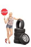 Junger weiblicher Mechaniker, der ein Stoppschild hält Stockfoto