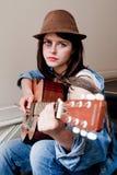 Junger weiblicher Musiker, der Gitarre spielt Stockfotos