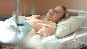 Junger weiblicher Patient, der im Krankenhausbett auf dem Tropfenfänger spricht mit einem Doktor liegt Stockbilder
