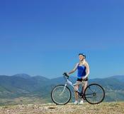 Junger weiblicher Radfahrer, der draußen mit einer Mountainbike aufwirft Lizenzfreie Stockfotografie
