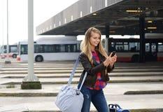 Junger weiblicher Reisender, der Handy betrachtet lizenzfreie stockbilder