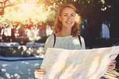 junger weiblicher Reisender mit nettem Lächeln neue Weise auf Atlas während des erstaunlichen Sommerabenteuers studierend Stockbild