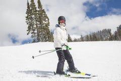 Junger weiblicher Skifahrer, der abwärts am Skiort Ski fährt Lizenzfreies Stockfoto