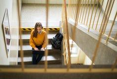 Junger weiblicher Student, der in der Schule auf Treppe, Versuch auf ihren Laptop schreibend sitzt getrennte alte Bücher Lizenzfreie Stockfotos