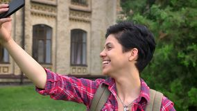 Junger weiblicher Student, der selfie nimmt und lustige Gesichter, stehend im Park nahe Universität, Lächeln tut, glücklich stock footage
