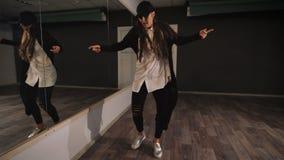 Junger weiblicher Tänzer im weißen Hemd, in der schwarzen Hose und schwarzen in der Kappe, die Jazz modernes Tanzen zeigt Mädchen