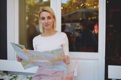 Junger weiblicher Tourist, der auf Karte den besten Weg nach den folgenden Ferien beim Sitzen im bequemen Straßencafé sucht Stockbild