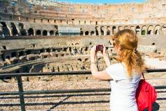 Junger weiblicher Tourist macht ein Foto innerhalb des Kolosseums in Rom Stockbilder