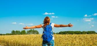 Junger weiblicher Tourist mit dem Rucksack, der den Abstand nahe einem Weizenfeld unter dem heißen Sommerhimmel untersucht stockfotos