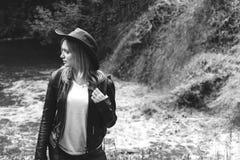 Junger weiblicher Tourist mit dem Rucksack und Cowboyhut, die den Fluss betrachtet, wusch weg die Brücke, die Überfahrt war unmög stockfoto