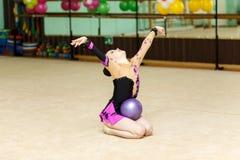 Junger weiblicher Turner, der geschickten Trick mit Ball auf Kunstturner tut Lizenzfreies Stockfoto