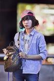 Junger weiblicher Verkäufer verkauft Taschen auf der Straße, Kunming, China Stockfotografie