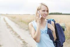 Junger weiblicher Wanderer, der Handy bei der Stellung auf Feld verwendet Lizenzfreie Stockfotos