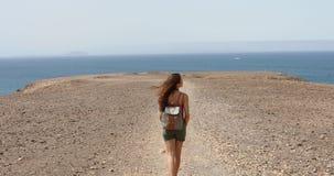 Junger weiblicher Wanderer, der Ozeanbrise genießt und Fuerteventura-Insel vor ihr schaut Wandererreisend-Mädchengehen stock video