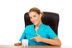 Junger weiblicher Zahnarzt, der Zahnmodell hält und hinter dem Schreibtisch sitzt stockbild