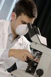 Junger Wissenschaftler, der am Mikroskop arbeitet Stockfotografie