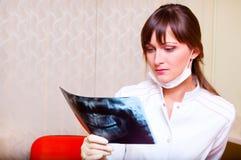 Junger Zahnarzt, der Röntgenstrahlabbildung betrachtet Lizenzfreies Stockfoto