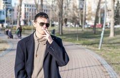 Junger zufälliger Rauchermann mit Sonnenbrille in der rauchenden Zigarette des schwarzen Mantels draußen im Park stockfotos
