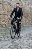 Junger zufälliger Geschäftsmann, der sein Fahrrad reitet stockfotos