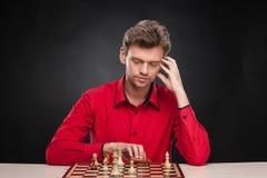 Junger zufälliger Mann, der über Schach sitzt Lizenzfreies Stockfoto