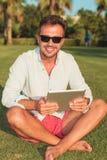 Junger zufälliger Mann, der auf der Rasenfläche hält eine Tablette sitzt Lizenzfreies Stockfoto