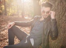 Junger zufälliger Mann, der auf einem Baum, seine Gläser reparierend sich lehnt Lizenzfreie Stockfotos