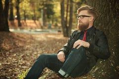 Junger zufälliger Mann, der auf einem Baum sich lehnt Stockfotografie