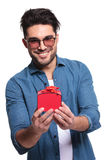 Junger zufälliger Mann, der ein kleines rotes Geschenk darstellt Lizenzfreies Stockfoto