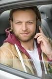 Junger zufälliger Mann, der am Handy im Auto lächelt und spricht Stockfotografie