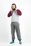 Junger zufälliger Mann in der Sportkleidung, die Hoodie hält Stockfoto